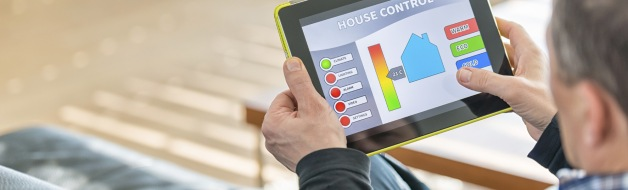 Man using digital tablet for remote house control